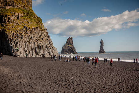 Vik, Iceland - September 5, 2018: The black sand beach of Reynisfjara and the mount Reynisfjall from the Dyrholaey promontory in the southern coast of Iceland.