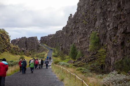 Thingvellir, Iceland - September 4, 2018. Visitors walk through Almannagja, the largest of the rifts that dissect this area where the continental plates of America and Europe are tearing slowly apart.