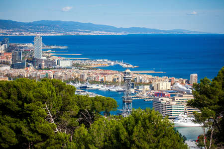 Panoramic cityscape of Barcelona (Spain) with harbour from the Montjuic mount in a sunny day. Aerial view.