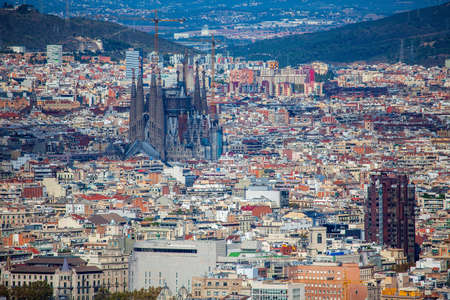 Panoramic cityscape of Barcelona (Spain) with Sagrada familia from the Montjuic mount in a sunny day. Aerial view.