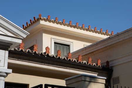Antefixes, traditional carved ornaments at the eaves of a roof of a house in Athens, Greece. Acroteria - decoration in the shape of palmette on the pediment of Greek building, decor element of architecture in classical warrant
