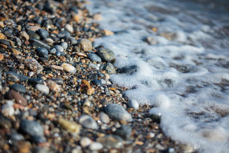 Pebble texture close up on the Mediterranean beach, very shallow depth of field Stock Photo