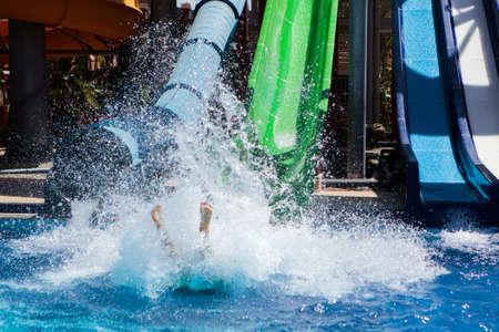 Colourful plastic slides in aquapark near the pool