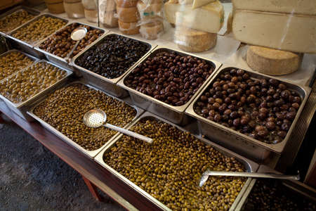 Assortment of olives on market in Greece. Text in greek on the bowls - type of olives and price.