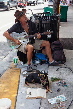 Key West, FL, USA - October 6, 2016: Street musian or man playing gitar with his dog in Key West, USA. Editorial