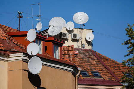 The old house rooftop with many satellite dishes and TV antennas in Vilnius, Lithuania. Sunny autumn day. Zdjęcie Seryjne