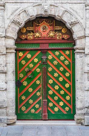 Door of the Brotherhood of Blackheads. Ornate green wooden door of old stone house in Tallinn, Estonia Stock Photo