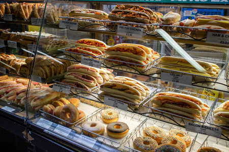 London, United Kingdom - May 4, 2019: Burgers, donuts and sandwiches in a shop glass counter. Shiny showcase of baked fastfood with prices.