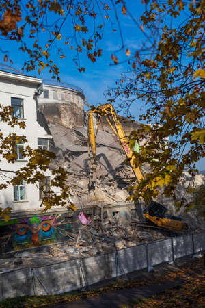 Vilnius, Lithuania - October 14, 2019: An excavator works at demolition site. An old soviet union building named Palace of Trade Unions is being demolished.