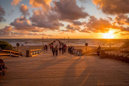 Palanga, Lithuania - July 12, 2020: Tourists are watching a sunset at a famous marine Palanga pier on the Baltic sea in the resort city Palanga.