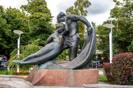 Palanga, Lithuania - July 12, 2020: Monument dedicated to Jurate and Kastytis (sculptor N. Gaigalaite, 1959) located in a square right next to the main tourist attraction - a bridge that leads to sunset.