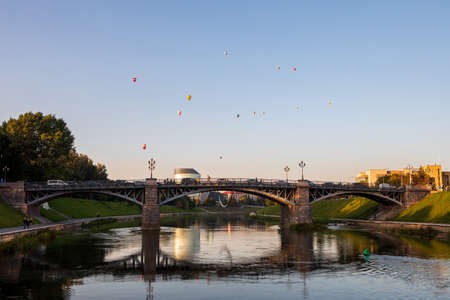 Vilnius, Lithuania - September 22, 2020: Zverynas Bridge and the sculpture The Ship-Crescent under it. Sculptor K. Vildziunas, 2010. Nice cityscape and flying hot air balloons are seen in the distance.