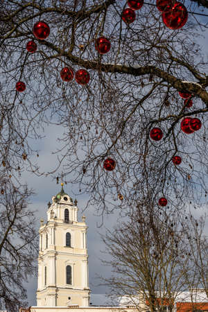 Tower of the Church of St. Johns surrounded with branches with red balls hanging. Vilnius, Lithuania