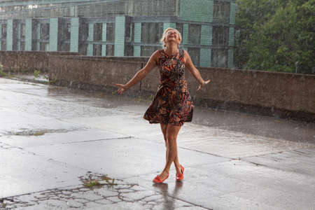 Attractive caucasian female dancing under the summer rain and enjoying with water drops