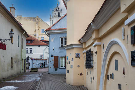 Vilnius, Lithuania - March 14, 2021: Tourists walk on Literatu street in Vilnius. Artworks mounted on the walls of this street dedicated to the literature workers: writers, poets, translators.