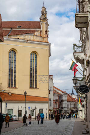 Vilnius, Lithuania - March 14, 2021: Tourists walk on Pilies Street, the oldest and most flamboyant street in the Old Town of Vilnius. St Johns church is seen on the left. Redakční