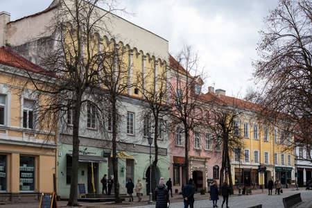 Vilnius, Lithuania - March 14, 2021: Tourists walk on Pilies Street, the oldest and most flamboyant street in the Old Town of Vilnius.