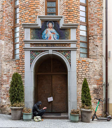 Vilnius, Lithuania - March 14, 2021: Beggar sits in front of the entrance of the Sanctuary of the Divine Mercy in Vilnius, Lithuania.