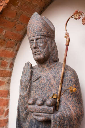 Vilnius, Lithuania - March 14, 2021: A sculpture of Saint Nicolas in the niche of the Church of St. Nicolas, the oldest church in Vilnius.