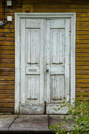 White weathered wooden door in an old yellow house Reklamní fotografie