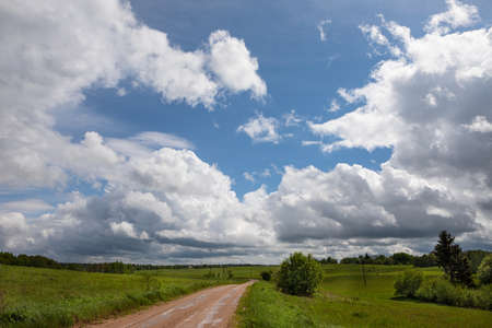 Rural landscape with unpaved road and green pastures in the summer. Big skies with the fluffy cummulus clouds. Lithuania, Zarasai district Zdjęcie Seryjne
