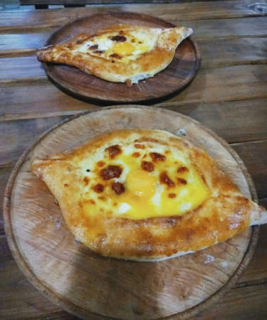 Georgian national dish khachapuri. Serve on a wooden dish. Foto de archivo