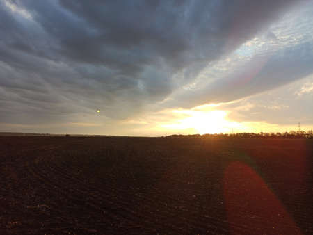 Sunset over a plowed field. Summer evening Foto de archivo