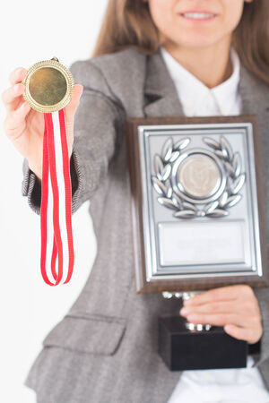 Happy smiling Young Businesswoman holds up her gold medal and award photo