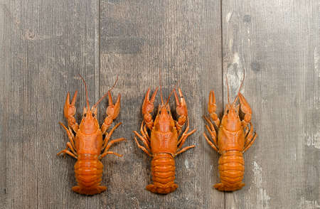 fluvial: Three red crayfishes in a row on old dark wooden table