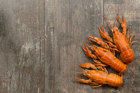 Three red crayfishes in the left-bottom corner on old dark wooden table Stock Photo
