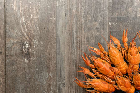 fluvial: Plate of red crayfishes on old dark wooden table in left-bottom corner
