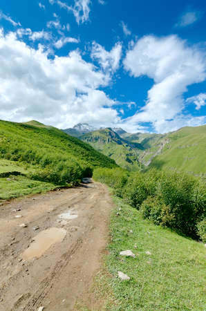 leading the way: Road with tire tracks leading to mountains and beautiful clouds. Puddle with small stones on the way