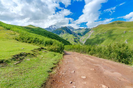 clay stone road in jungle: Road with tire tracks leading to mountains and beautiful clouds. Puddle with small stones on the way