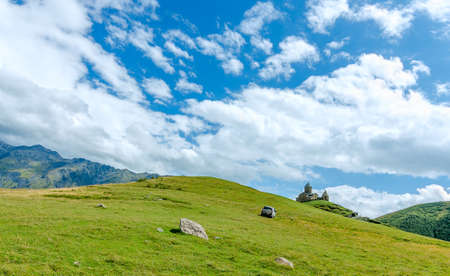 clay stone road in jungle: View on small church in mountains with beautiful clouds. A car and stones on the way
