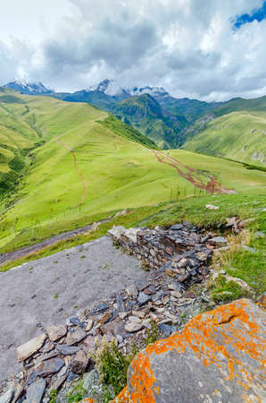 clay stone road in jungle: View on valley in Georgian mountains. Road leads to beautiful mountains.