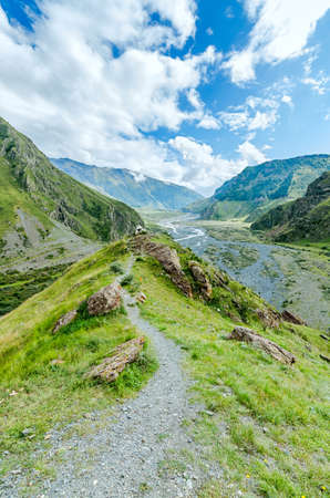 clay stone road in jungle: Path to big cross in mountains of Georgia. Beautiful blue sky and white clouds. View on river
