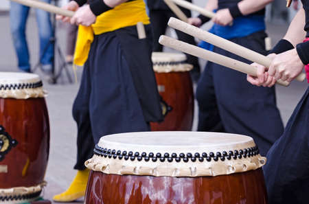 Group of japanese musicians are playing on traditional japanese percussion instrument Taiko or Wadaiko drums. The drumsticks are in the hands.