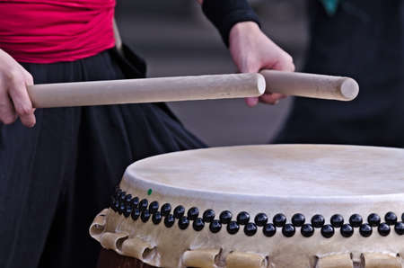 percussion instrument: Group of japanese musicians are playing on traditional japanese percussion instrument Taiko or Wadaiko drums. The drumsticks are in the hands.