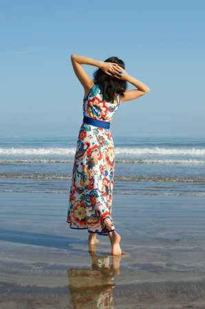 shoeless: Young girl in beautiful dress looking at the ocean and city