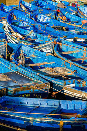sea fishing: Beautiful array of blue boats in Essaouira port, Morocco Stock Photo