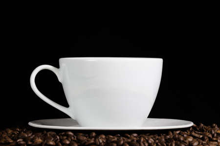 stays: Cup of coffee stays on coffee beans over dark background. Side view. Stock Photo