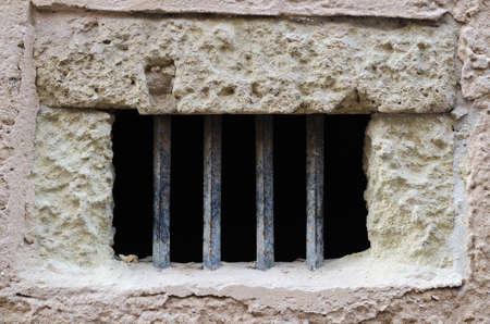 rejas de hierro: Ventana con barras de hierro en la vieja fachada con ladrillos blancos