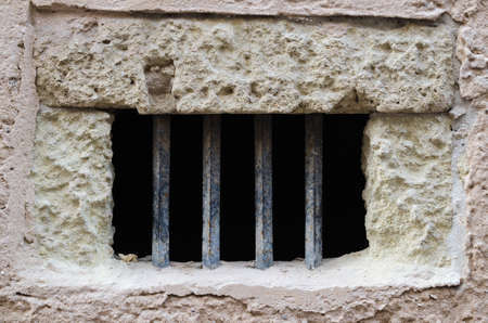 iron barred: Window with iron bars on old facade with white bricks Stock Photo