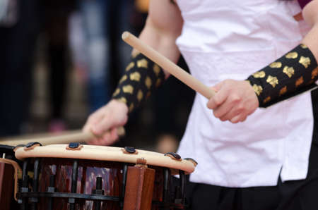 drumming: Japanese artist is drumming on traditional taiko drums. Drumsticks beating on a traditional drum