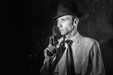 trench coat: Handsome detective in trench coat holding a gun in the dark. Noir film style. Black and white photography Stock Photo