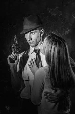 A detective with a gun and his beautiful woman leaning on him. Studio shot. Noir style. Black and white photography