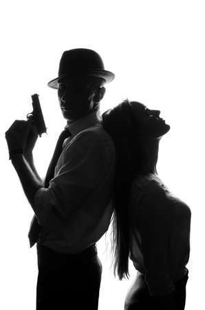 A silhouettes of a man detective with a gun and his beautiful woman leaning on him. Studio shot. Isolated on white background