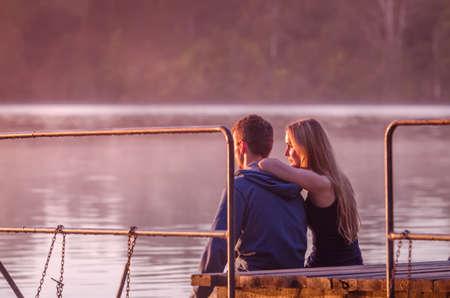 mujer mirando el horizonte: Vista trasera de una pareja rom�ntica, sentado en el muelle y disfrutar de la puesta de sol impresionante cerca del lago