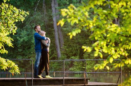 iluminado a contraluz: Hombre que abraza a su novia al atardecer en un muelle cerca del agua
