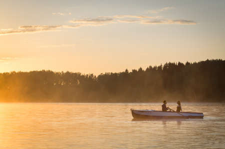 Romantic golden river sunset with fog and loving couple on small boat backlit by sunlight